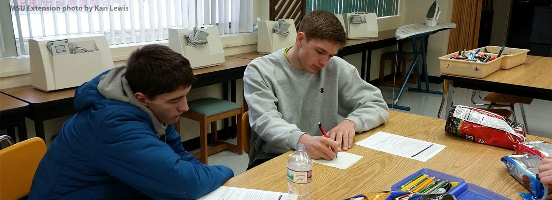 Two teen 4-H members working on a project together at a table.